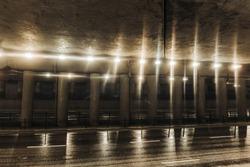 Horror tunnel background. Dark pavement tunnel with bright light. Scary walkway under the bridge. Grunge urban bridge construction. Wet road after rain.