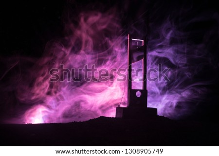 Horror view of Guillotine. Close-up of a guillotine on a dark foggy background. Execution concept #1308905749