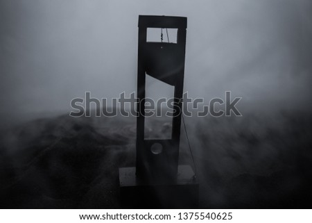 Horror view of Guillotine. Close-up of a guillotine on a dark foggy background. Execution concept #1375540625