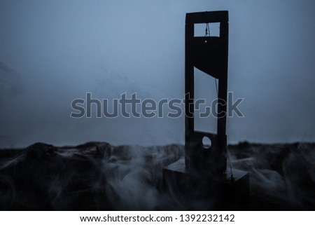 Horror view of Guillotine. Close-up of a guillotine on a dark foggy background. Execution concept #1392232142