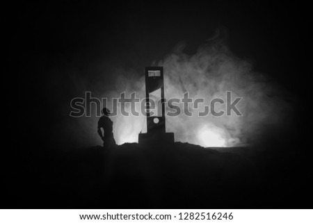 Horror view of Guillotine. Human at guillotine on a dark foggy background. Execution concept #1282516246