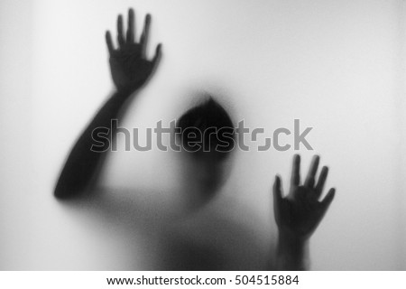 Horror woman behind the matte glass in black and white. Blurry hand and body figure abstraction.Halloween background.Black and white picture