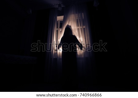 Horror woman in window wood hand hold cage scary scene halloween concept Blurred silhouette of witch. Horror theme