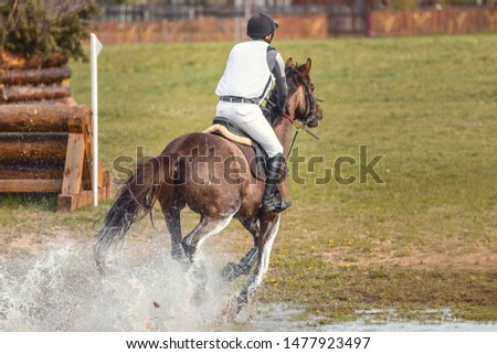 horse and rider galloping in water during eventing competition