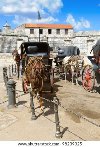 Horse drawn carriages parked in Plaza de Armas, Old Havana