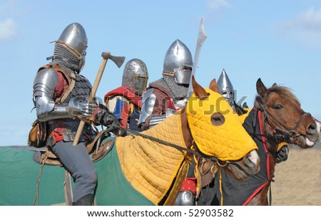 Horse knights in the heavy armour, armed with swords and the axes, prepared for fight