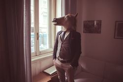 horse mask man in front of window at home