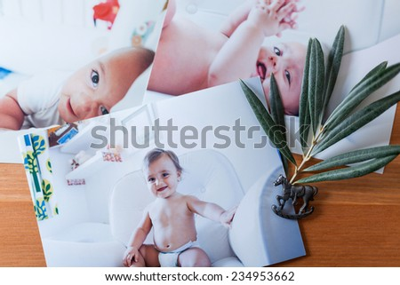 horse pin and baby portraits on a wooden table