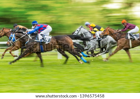 Horse racing outdoor derby with jockeys heading to finish line. Outdoor sport and competition.