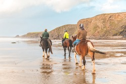Horse ride on the beach in Wales at sunset - Three people with horses at seaside, enjoying a horseback ride on a beautiful day in the UK - Sport, leisure and travel concepts