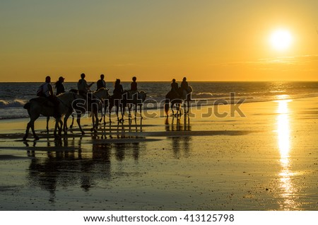 Horse riding , sunset reflection on the beach of Mazagon , Huelva , Andalusia, Atlantic coast , Spain