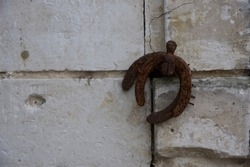 Horse shoes: two old horse shoes hang upside down on a French shutter retaining catch