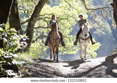 Shutterstock Horseback riders; two attractive women ride horses with backlit leaves behind them