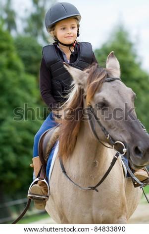 Horseback riding - little girl is riding a horse