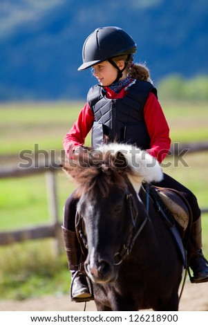 Horseback riding, lovely equestrian - young girl is riding a pony