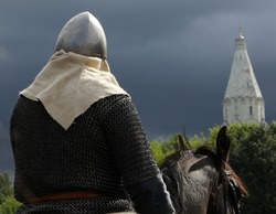 Horseman in armor on a background of the church and stormy sky
