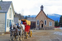 Horses pulling old wagon in historic town of Barkerville, British Columbia Canada