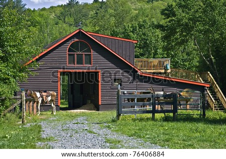 Horses tied in front of a log barn with living quarters upstairs.