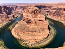 Horseshoe Bend is the name of the place where the Colorado River entrenched in the shape of a horseshoe near the town of Page, Arizona, United States.The boat floating on the river looks small.