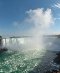 Horseshoe falls, a part of Niagara Falls on Niagara river ,with a tall cloud of water splashes in a sunny autumn day