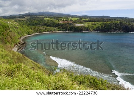 Horseshoe shaped Honolua Bay on Maui, Hawaii shows beautiful azure water and coral reef underneath