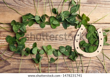 Horseshoe with clover leaf frame on old wooden boards. St. Patricks day, lucky charms. Space for text.
