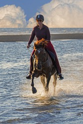 Horsewoman / female horse rider on horseback galloping through water on the beach with approaching thunderstorm