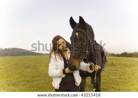 Horsewoman holds the horse's bridle.