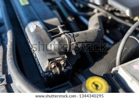 Hose connecting the car radiator with the engine, In the background the engine compartment.