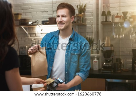 hospitable barista man standing behind bar sells hot coffee drink and lunch in paper bag to woman client for takeaway , woman pays with bank card.