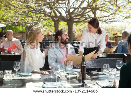 Hospitable waitress helping visitors with menu on outdoor terrace of country restaurant