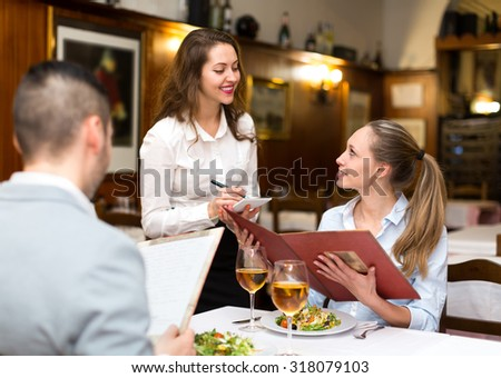 Hospitable waitress taking an order from a couple in a rural restaurant
