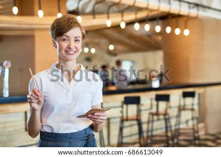 Hospitable waitress with notepapers and pencil ready to take your order