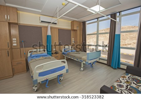 Hospital beds in a private hospital ward with sofa