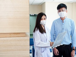 Hospital clinic or laboratory doctor scientist female wear mask inquire is looking at camera report patient treatment family man health care medical protection covid-19 corona virus disease vaccine