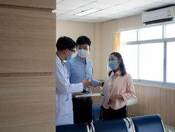 Hospital clinic or laboratory doctor scientist male wear mask  inquire is talking patient treatment family couple man and woman health care medical protection covid-19 corona virus disease vaccine