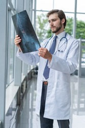 hospital doctor holding patient's x-ray film, radiologist studying x-ray results