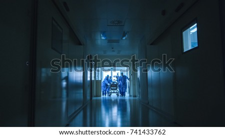 Hospital Emergency Team Carrying Stretcher with Patient Through Dark Hospital Hall.