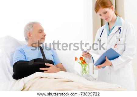 Hospital - female doctor examine senior patient with broken arm