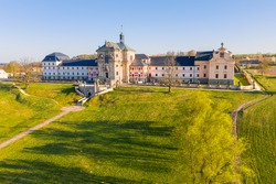 Hospital Kuks from drone in early evening sun. Spring sunlit landscape. Museum of czech pharmacy - baroque spa building.