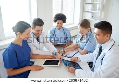 hospital, medical education, health care, people and medicine concept - group of happy doctors with tablet pc computers meeting at medical office