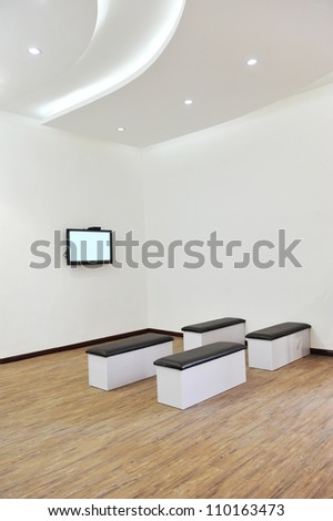 Hospital or clinic waiting room with stools and flat screen TV.