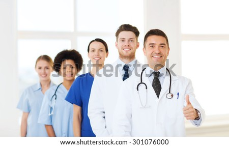 hospital, profession, people and medicine concept - group of happy doctors at hospital showing thumbs up gesture