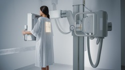 Hospital Radiology Room: Beautiful Multiethnic Woman Standing in Medical Gown in the X-Ray Machine. Adult Female Undergoes Healthcare Exam and is Scanning Chest, Heart, Lungs in Modern Clinic Office.