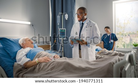 Hospital Ward: Friendly Black Doctor Talks with Elderly Caucasian Patient Resting in Bed, Asks Health Care Questions. Doctor Uses Tablet Computer. Old Man Fully Recovering after Successful Surgery