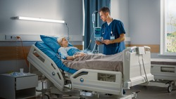 Hospital Ward: Friendly Male Nurse Talks to Beautiful Female Patient Resting in Bed. Male Nurse or Physician Uses Tablet Computer, Does Checkup, Woman Recovering after Successful Surgery