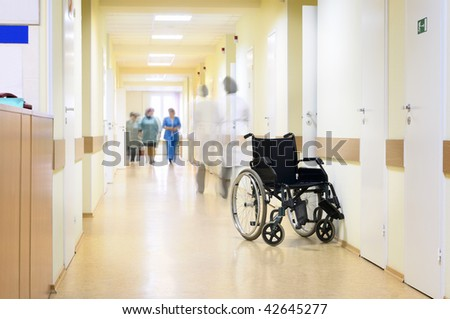 Hospital, wheelchair and unrecognizable people. - stock photo