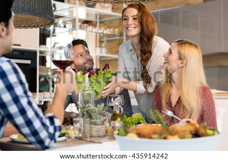 Host woman serving salad to guests at home. Smiling woman serving salads to her friends at home. Happy smiling people eating together for lunch. Group of friends enjoying meal at home together