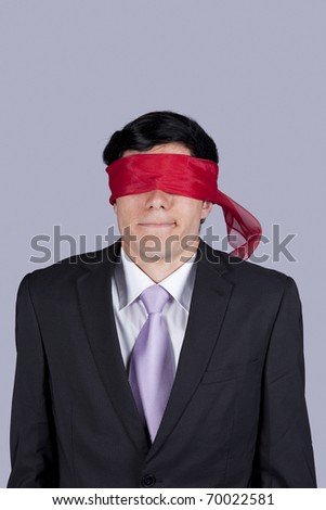 Hostage businessman with a red blindfold covering his eyes (isolated on gray)