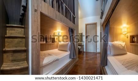 Hostel dormitory beds arranged in dorm room with white plain bunk bed in dormitory.Hostel dormitory have many beds arranged in one room. Clean hostel small room with wooden bunk beds. small hotel